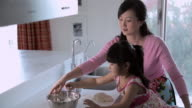 MS Mother and daughter making food together in kitchen / China