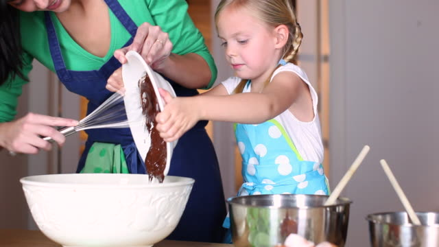 MS Mother and daughter (4-5) pouring chocolate into bowl / Brussels, Brabant, Belgium