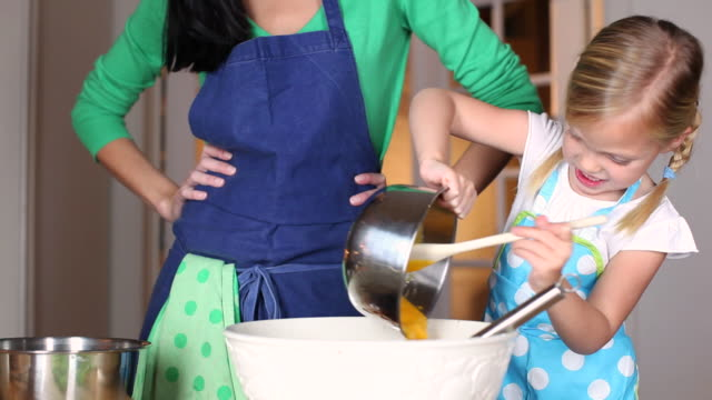 MS Mother and daughter (4-5) pouring egg mixture into bowl / Brussels, Brabant, Belgium