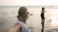 Mother and daughter practise yoga moves on beach, surf behind