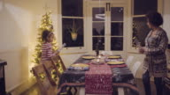 Mother and daughter prepare Christmas dinner table