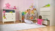 HD DOLLY: Mother and Daughter Putting Toys In Drawer
