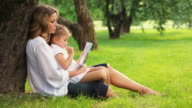 Mother and daughter reading book in park