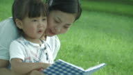 Mother and daughter reading book, sitting on grass