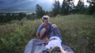 Mother and daughter relax together in mountain meadow