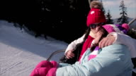Mother and daughter rides on ski lift on winter vacation