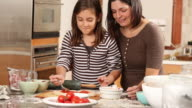 Mother and daughter rolling pizza dough