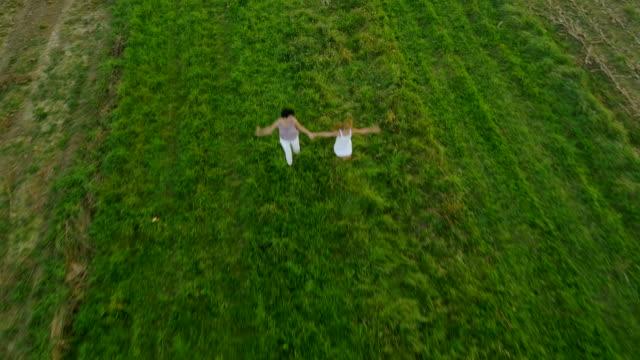 AERIAL Mother And Daughter Running In The Meadow