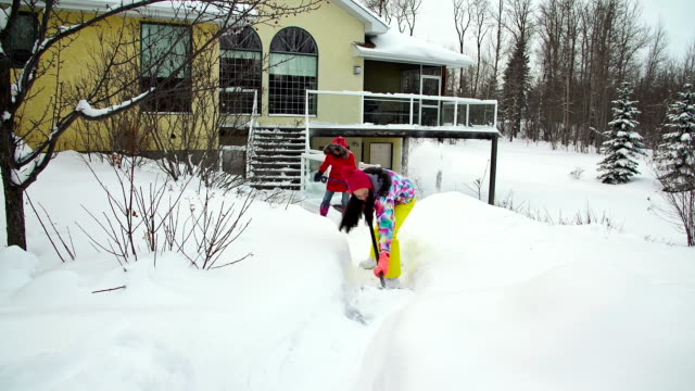 Mother and daughter shoveling snow off house deck and walkway