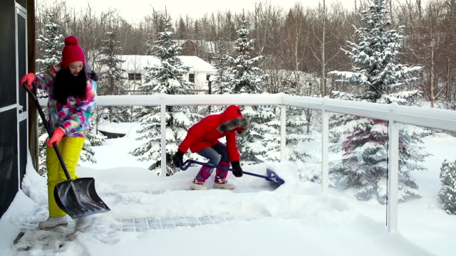 Mother and daughter shoveling snow off house deck