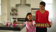 MS Mother and daughter showing freshly baked cookies