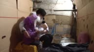 A mother and daughter sit inside a makeshift bomb shelter in the basement of their house
