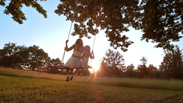 SLO MO Mother and daughter swinging at sunset