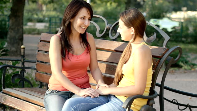 Mother and daughter talking outdoors in summer park