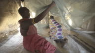 Mother and Daughter using mosquito net. Kenya. Africa.