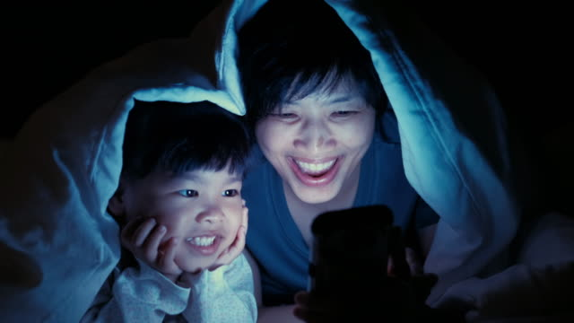 Mother and Daughter using smart phone under blanket