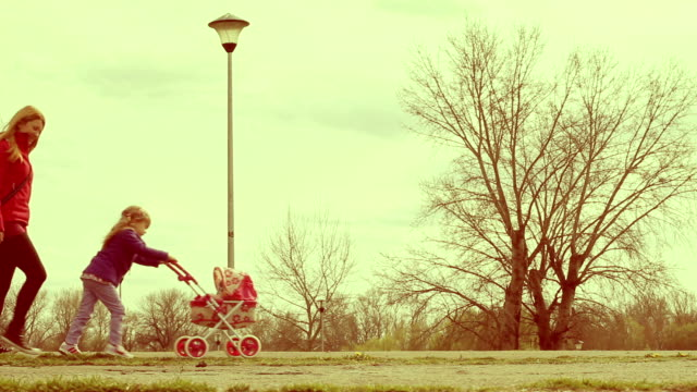 Mother and daughter walking in park with doll stroller