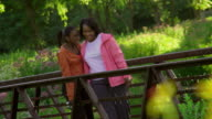 MS PAN Mother and daughter (8-9) walking on bridge in park / Rockford, Illinois, United States
