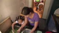 MS, HA, Mother and daughter (6-7) washing vegetables in kitchen sink, man watching television in background, Shanghai, China