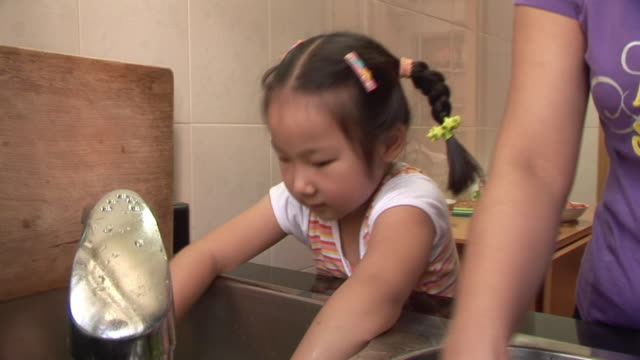 CU, TU, Mother and daughter (6-7) washing vegetables in kitchen sink, Shanghai, China