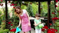 HD: Mother and Daughter Watering Flowers in a backyard.
