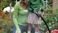 TD Mother and Daughter Watering Plants in Vegetable Garden / Richmond, Virginia, USA