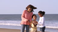 Mother and daughters talking on beach