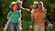 Mother and father giving daughters piggyback rides on wooded trail