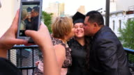 MS Mother and father kissing graduating daughter during family celebration