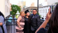 MS TS Mother and father posing for picture with graduating daughter during celebration dinner on restaurant deck