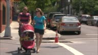 A mother and father push a baby stroller in the Park Slope neighborhood of Brooklyn