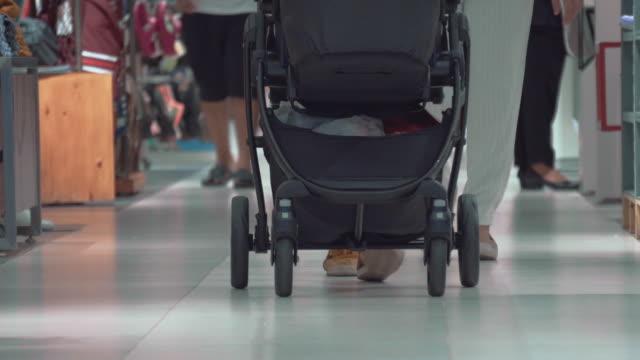 Mor och far går med barnvagn och baby i köpcentrum
