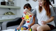 Mother and girl playing with colored blocks.