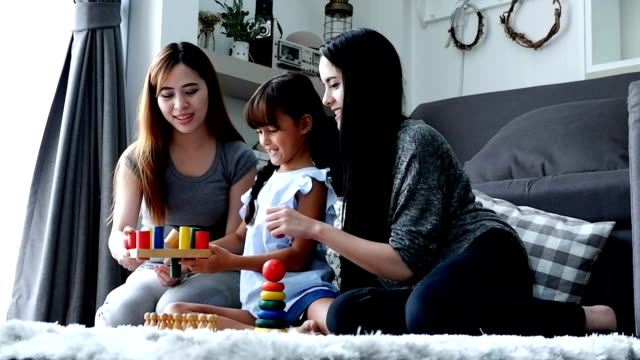 Mother and girl playing with colored blocks