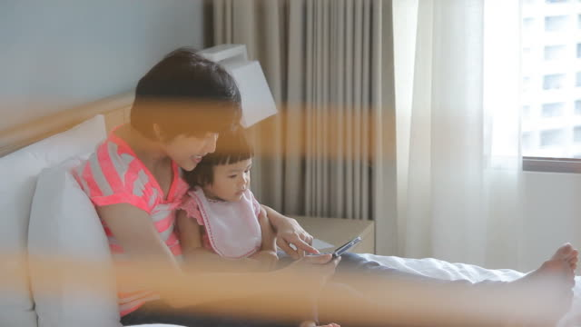 HD : Mother and her baby using Smart Phone