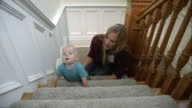 Mother and her infant son playing on the stairs