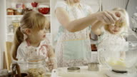 Mother and Her Little Daughters Preparing Cookies in the Kitchen