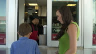 Mother and her son buying soda at window of a fast food restaurant