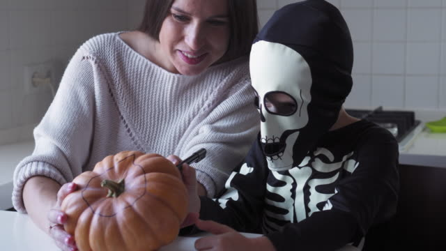 Mother and her son drawing the jack-o-lantern face on pumpkin