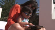Mother and his girl playing with Digital Tablet.