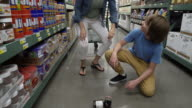 Mother and son finding a broken jar in a warehouse supermarket