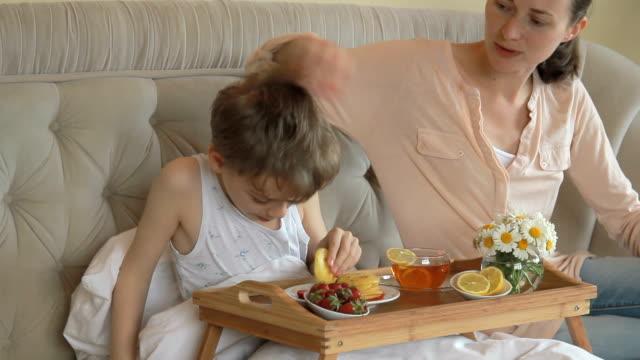 Madre e figlio, avendo colazione a letto