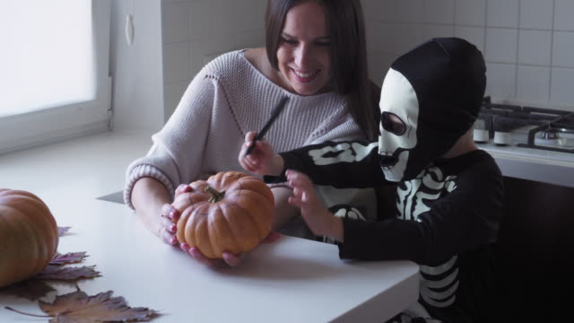 Mother and son having fun while drawing on halloween pumpkin