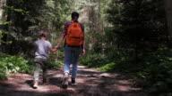 Moeder en zoon hand in hand op wandelpad