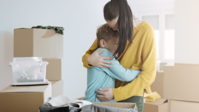 Mother and son hugging and putting clothes in cardboard box
