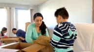 Mother and son packing belongings into cardboard boxes while moving from suburban home