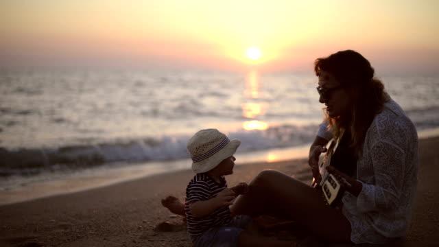 Moeder en zoon een gitaar spelen op het strand