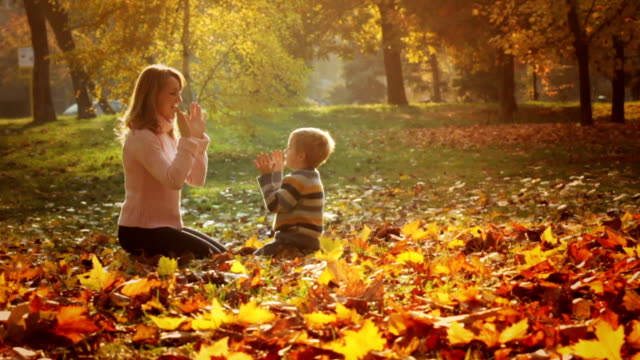 Mother and son playing clapping game in the park