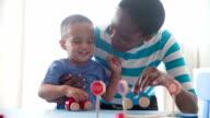 Mutter und Sohn spielen mit Holz Spielzeug-Autos wie zu Hause fühlen.
