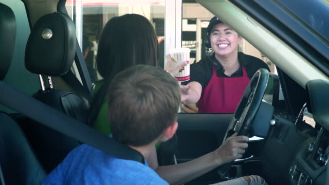 Mother and son receiving food order from employee of a fast food drive-through